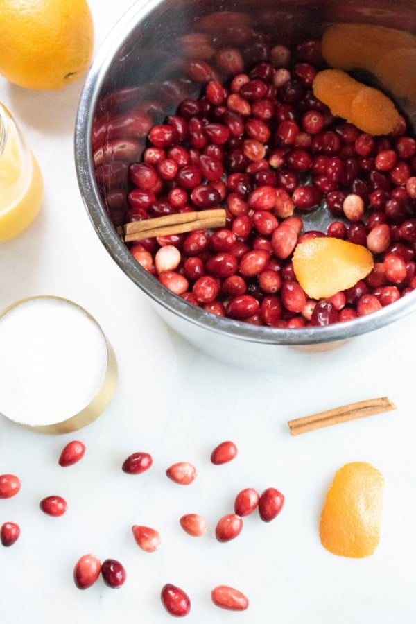 cranberries,cinnamon stick, orange peel, sugar, orange juice in an instant pot on a white table with these same ingredients on the table too