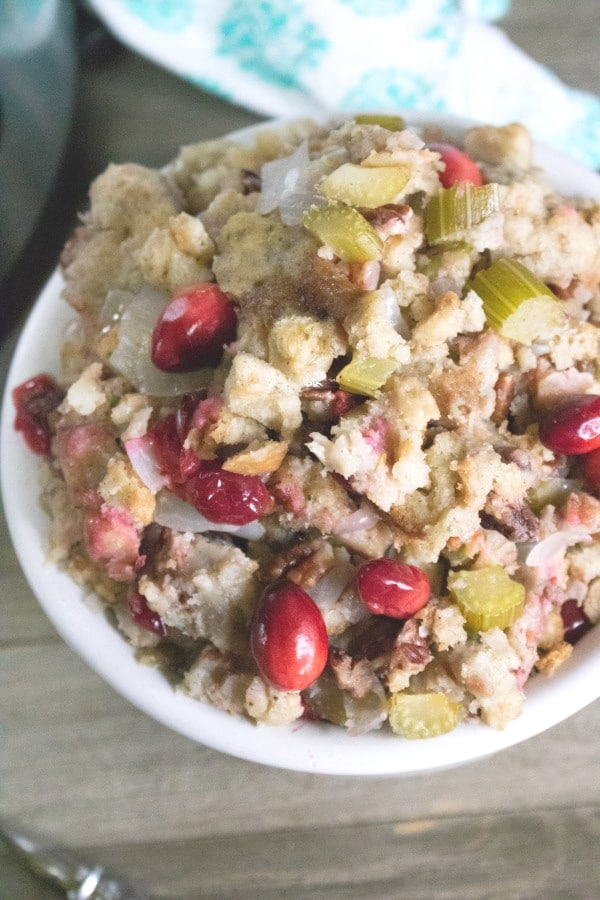 close up view of stuffing in a white bowl on a brown table with an instant pot and green linen in the background