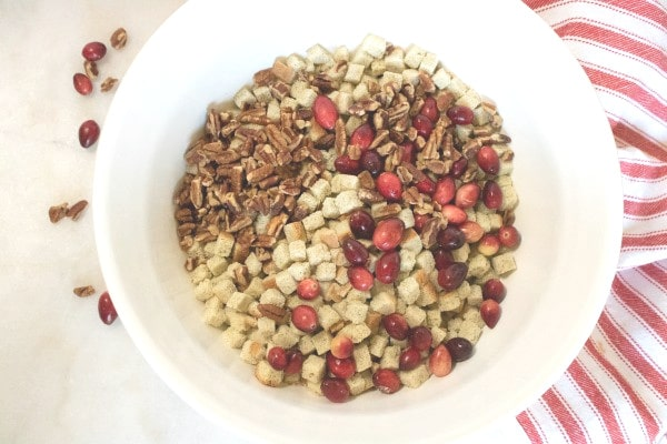 bread cubes, cranberries and nuts in a white bowl with more cranberries and nuts next to it on the white counter and also a red and white linen