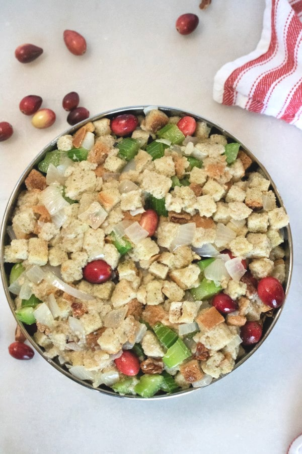 stuffing in a steamer pan with more cranberries and nuts next to it on the white counter and also a red and white linen