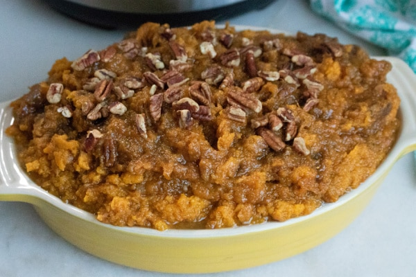 sweet potato casserole topped with pecans in a yellow dish on a white counter with an instant pot and blue and white linen in the background