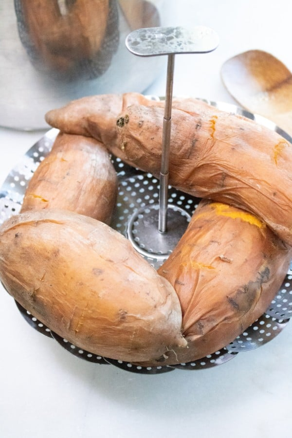 sweet potatoes on a steamer basket on a white counter with an instant pot and wooden spoon in the background