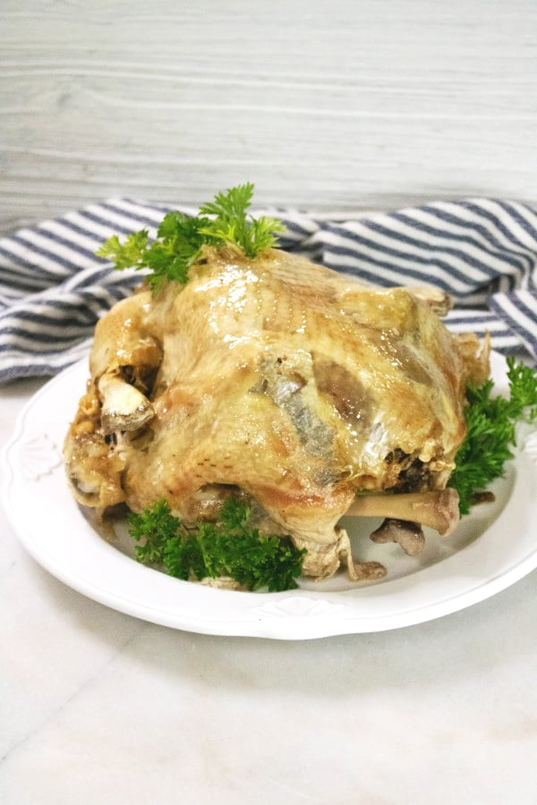a whole turkey on a white plate on a white counter next to a striped cloth