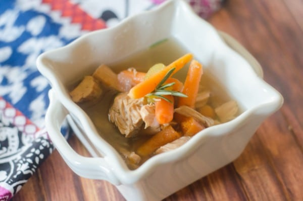 turkey soup topped with sliced carrots in a white bowl on a wood table with a multi-colored cloth in the background