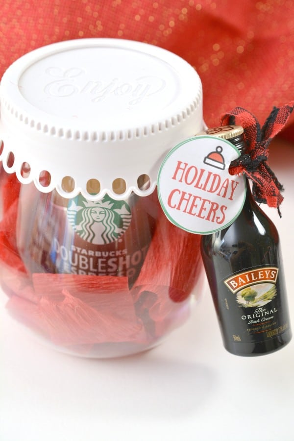 a can of Starbucks coffee surrounded by red crepe paper in a glass jar with a white lid with a bottle of Baileys liquer tied to it with a red ribbon and a Holiday Cheers tag with a red cloth behind it