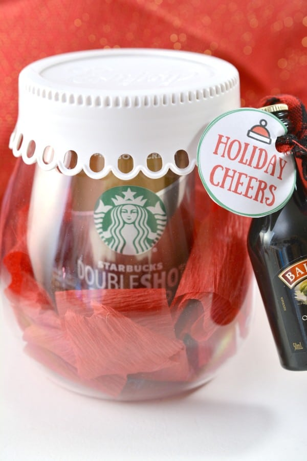 a can of Starbucks coffee surrounded by red crepe paper in a glass jar with a white lid with a bottle of Baileys liquor tied to it with a red ribbon and a Holiday Cheers tag with a red cloth behind it
