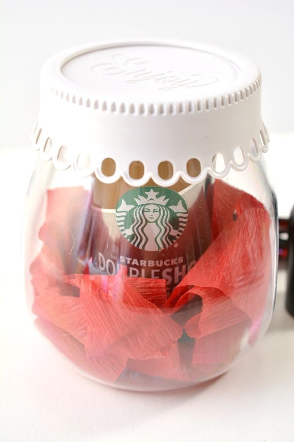 a glass jar with a white lid with a can of Starbucks coffee in it surrounded by red crepe paper on a white background