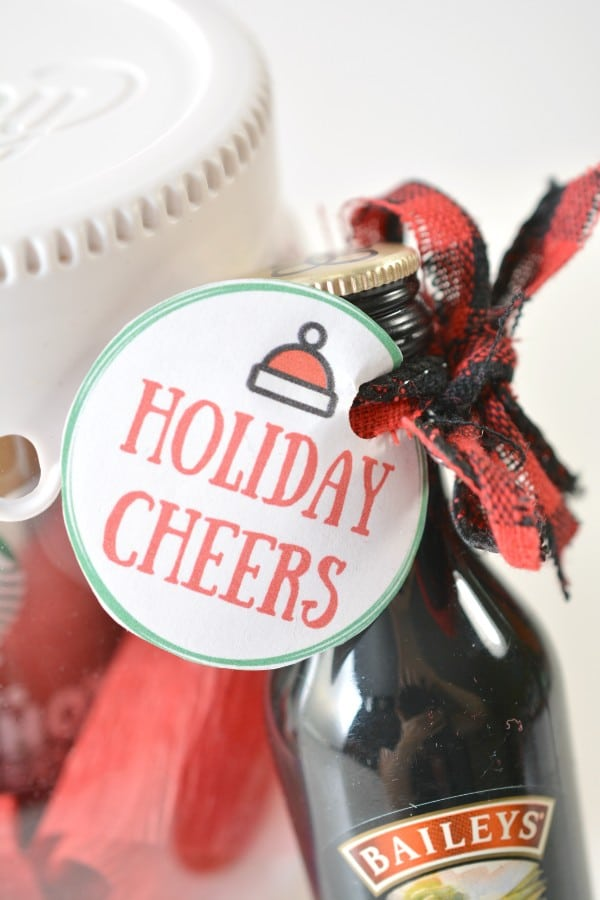 a closeup of a paper circle with text reading Holiday Cheers on it with a Santa hat graphic at the top tied with a ribbon to a glass jar and a bottle of Baileys liquer