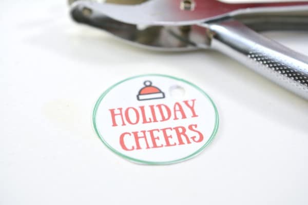 a paper circle with text reading Holiday Cheers on it with a Santa hat graphic at the top with a hole punch in the background