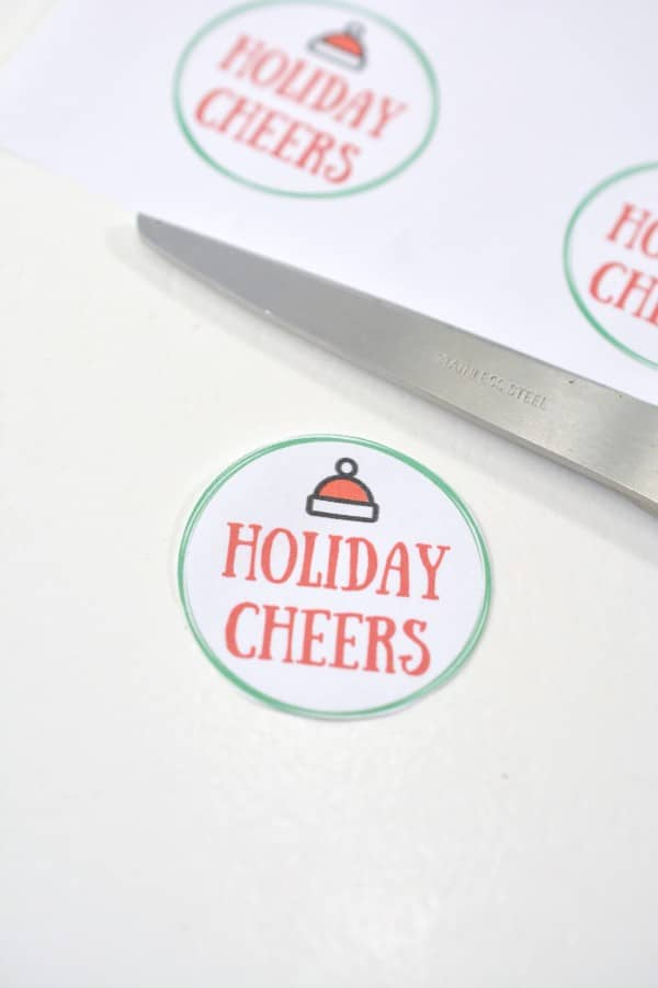 a paper circle with text reading Holiday Cheers on it with a Santa hat graphic at the top with scissors and a printable with more of those circles on it in the background
