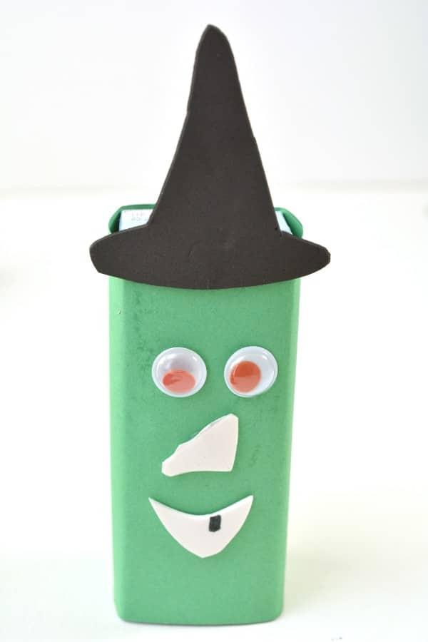 a witch made out of a juice box, construction paper, foam and googly eyes, with a white background