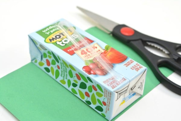 a juice box on green construction paper next to scissors on a white background