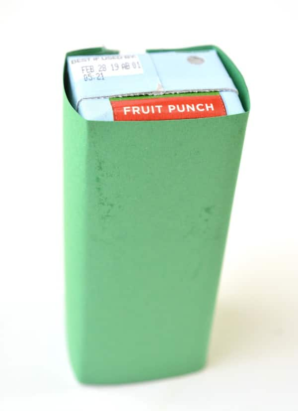 a juice box wrapped with green construction paper on a white background
