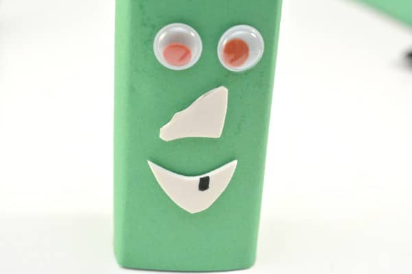 a juice box wrapped with green construction paper with googly eyes and white foam glued on to look like a nose and mouth, with a black spot on it as a tooth on a white background