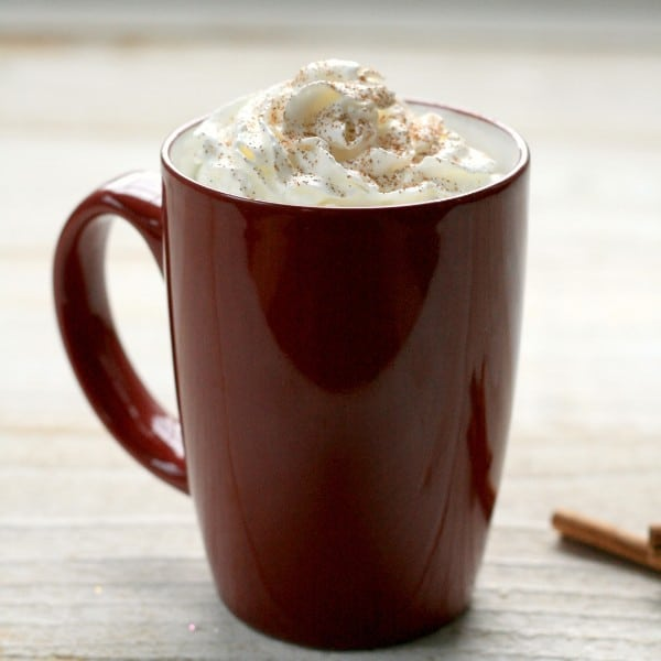 hot chocolate in a red mug topped with whipped cream with cinnamon sticks next to it on a table