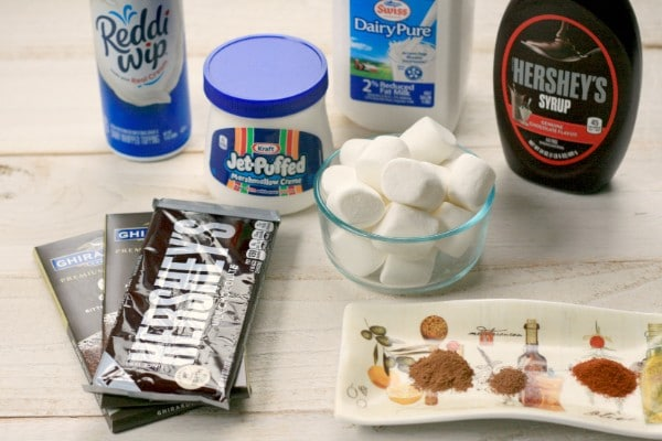 containers of reddi whip, marshmallow creme, milk, chocolate syrup and chocolate bars, a glass bowl of marshmallows, and a tray of spices all on a wood table