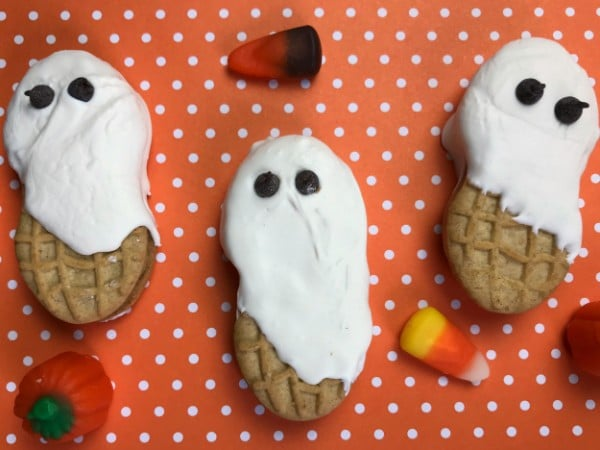 nutter butter cookies decorated with white frosting and mini chocolate chips to look like ghosts on an orange and white polka dotted background with candy corn and pumpkins next to them