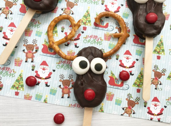 nutter butters coated with chocolate with pretzel antlers, candy eyes and a red m&m nose on a stick, made to look like a reindeer on a piece of Christmas paper