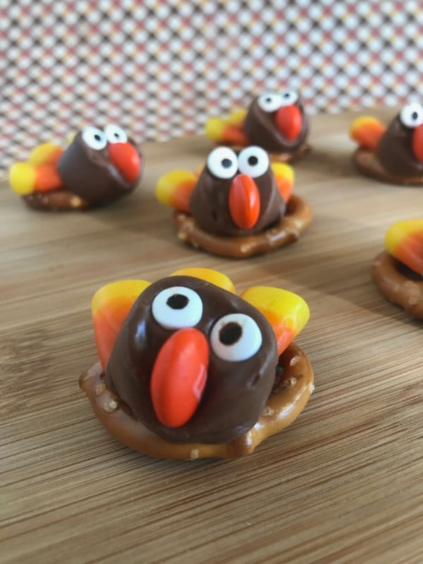 pretzels on a wood table topped with rolos decorated with candy eyes, an M&M nose, candy corn feathers to look like a turkey