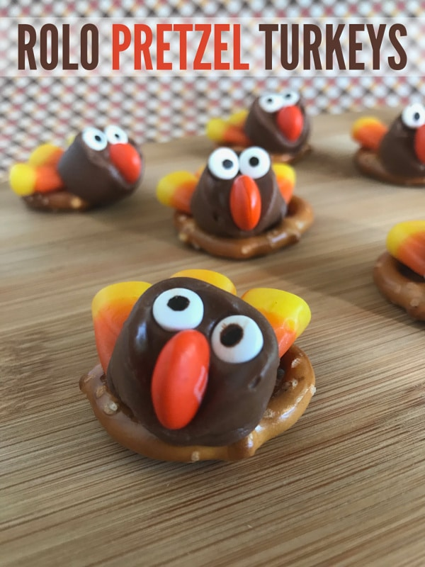 pretzels on a wood table topped with rolos decorated with candy eyes, an M&M nose, candy corn feathers to look like a turkey with title text reading Rolo Pretzel Turkeys