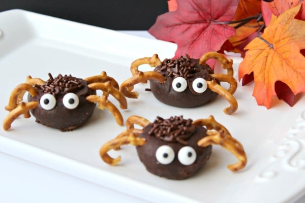 mini chocolate donuts decorated with chocolate frosting, sprinkles, candy eyes and pretzels to look like spiders on a white tray with fake leaves in the background
