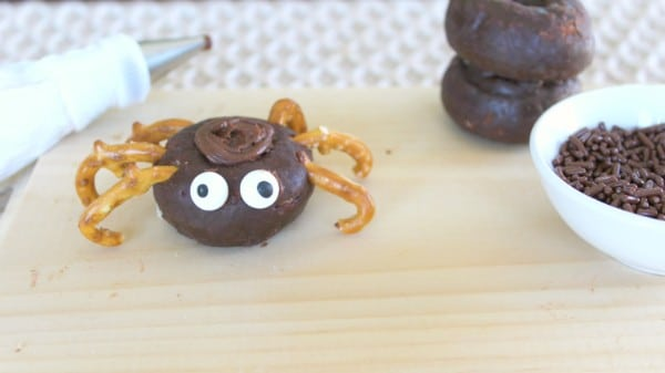 a mini chocolate donut  topped with chocolate frosting with broken pretzels stuck in the sides to look like spider legs on a brown cutting board with another donut and a white bowl of chocolate sprinkles int the background
