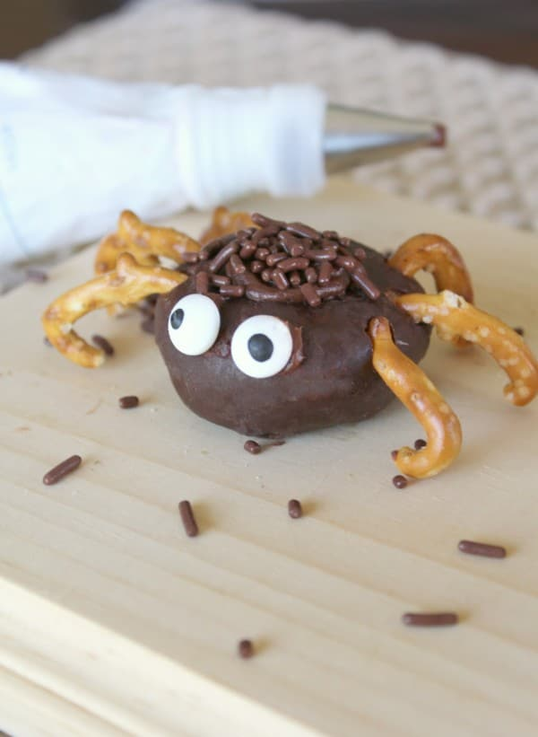 a mini chocolate donut decorated with chocolate frosting and sprinkles, pretzels and candy eyes to look like a spider on a brown cutting board with a pastry bag in the background