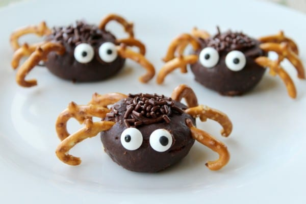 three mini chocolate donuts decorated with chocolate frosting and sprinkles, pretzels and candy eyes to look like spiders on a white plate