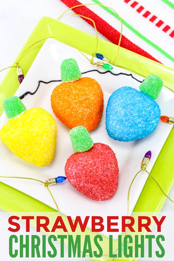 strawberries coated with colored sugar with a green gumdrop on top to look like Christmas lights on a white and yellow plate surrounded by mini Christmas lights on a gold chain with title text reading Strawberry Christmas Lights