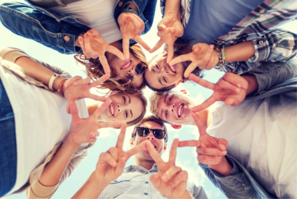 a group of teens in a circle showing the peace sign to a camera below them