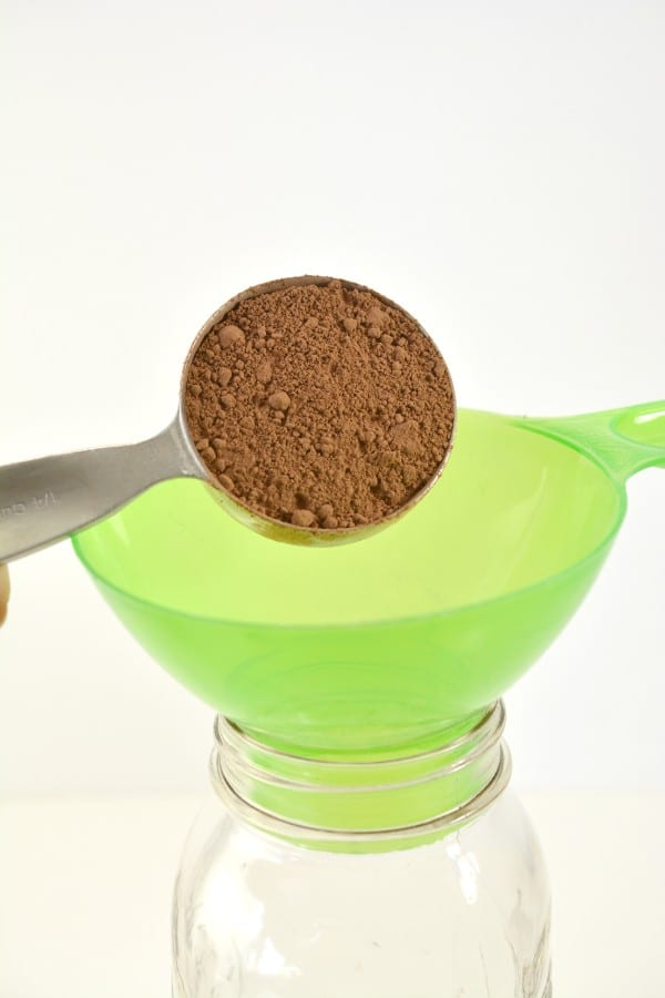 unsweetened cocoa being poured into a glass jar through a funnel