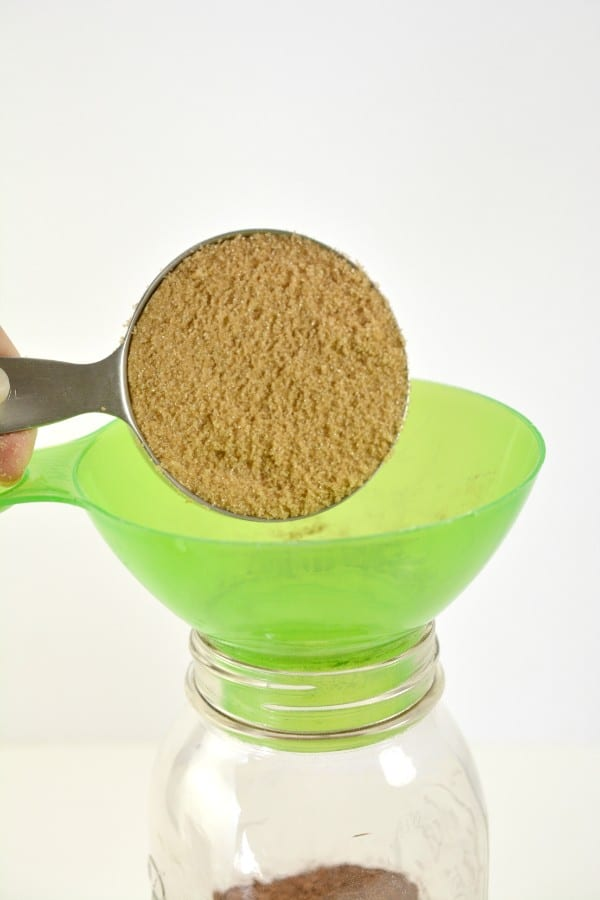 brown sugar being poured into a glass jar through a funnel