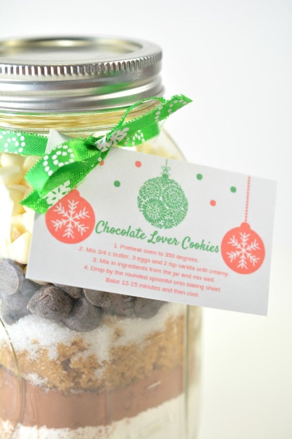 a mason jar filled with layered ingredients to make cookies with a card tied on it with a green ribbon
