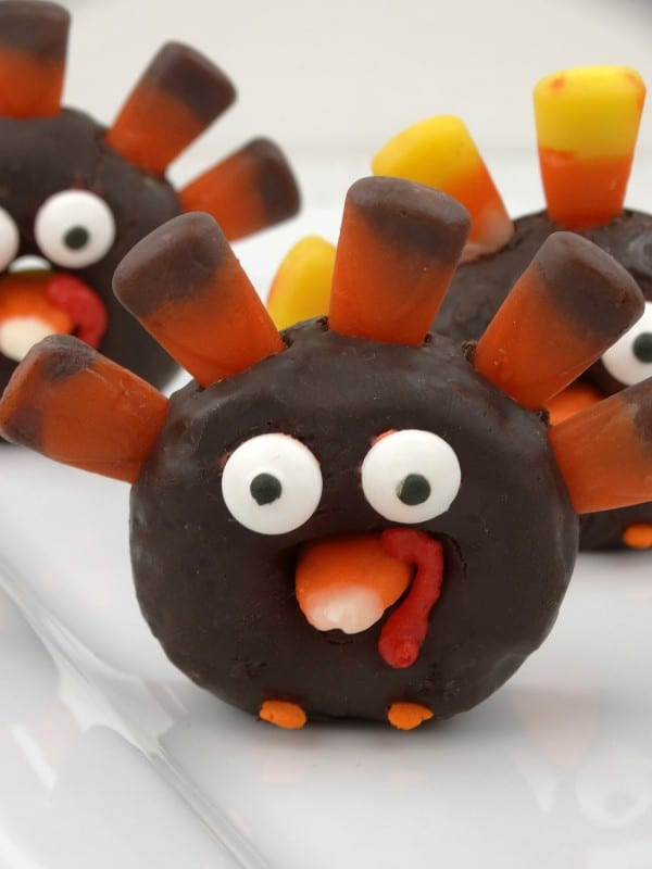 a closeup of mini chocolate donuts decorated with candy corn and candy eyes to look like a turkey on a white plate