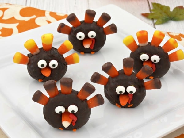 mini chocolate donuts decorated with candy corn and candy eyes to look like a turkey on a white plate