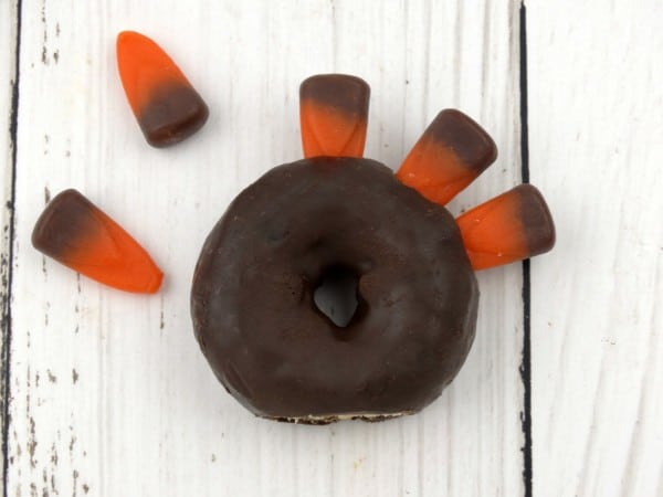 a mini chocolate donut with candy corn stick in the top of it and some more on the table