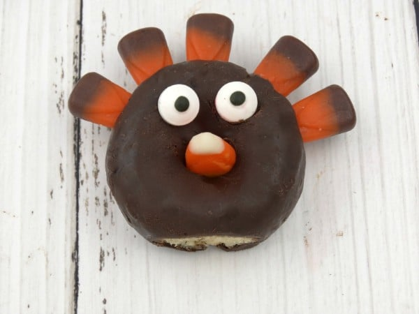 a mini chocolate donut with candy corn stick in the top of it, with candy eyes and a candy corn nose on a table