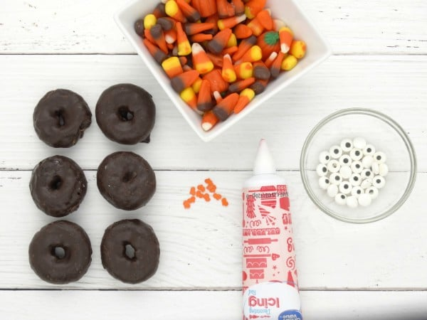 mini chocolate donuts, bowls of candy corn and candy eyes, orange sprinkles and icing all on a table