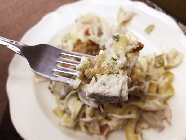 a fork with some turkey noodle casserole on it above a white plate of turkey noodle casserole on a brown table