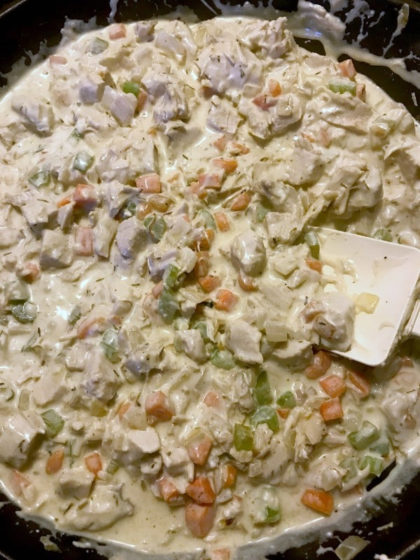 turkey noodle casserole in a skillet being stirred with a spatula