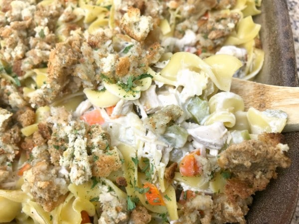 a close up of Turkey Noodle Casserole in a baking dish with a wooden spoon in it
