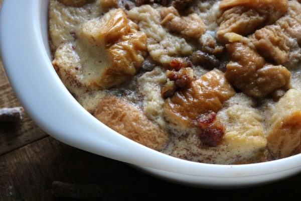 a close up view of bread pudding in a white bowl on a table