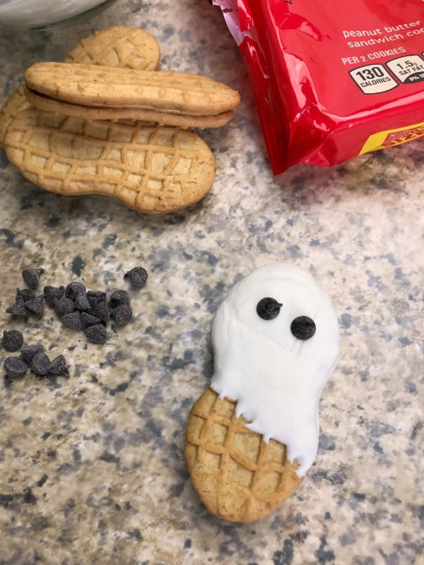 a package of nutter butters, three nutter butters, a nutter butter decorated with white frosting and mini chocolate chips to look like a ghost, more mini chocolate chips, all on a brown kitchen counter