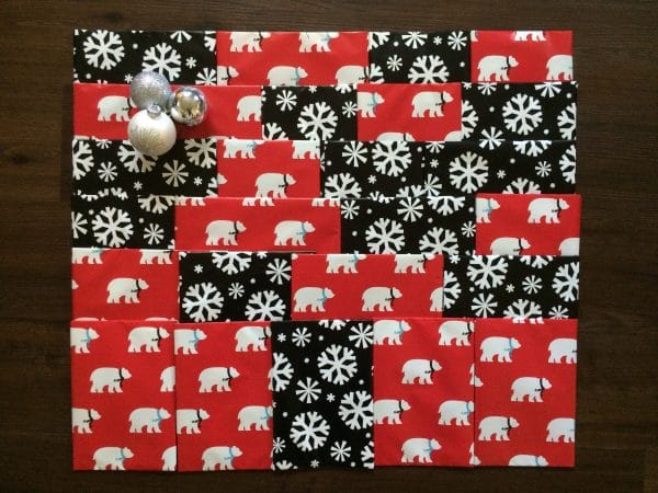 a square wrapped in polar bear and snowflake paper on a brown background