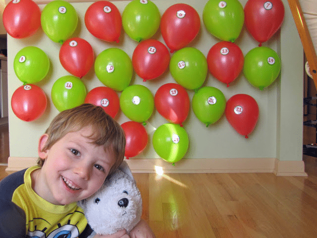 a boy holding a white teddy bear with a wall full of red and green balloons with paper numbers on them behind him