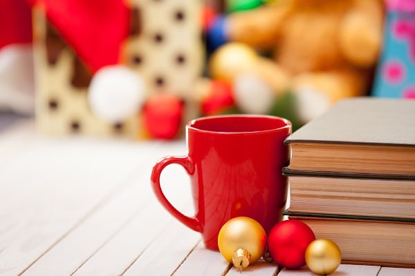 a red mug next to some ornaments and a stack of books on a wood surface with more toys in the background