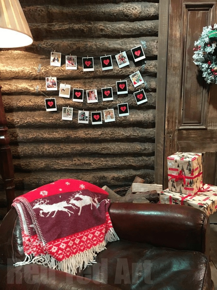 a living room in a log cabin with pictures strung across the wall