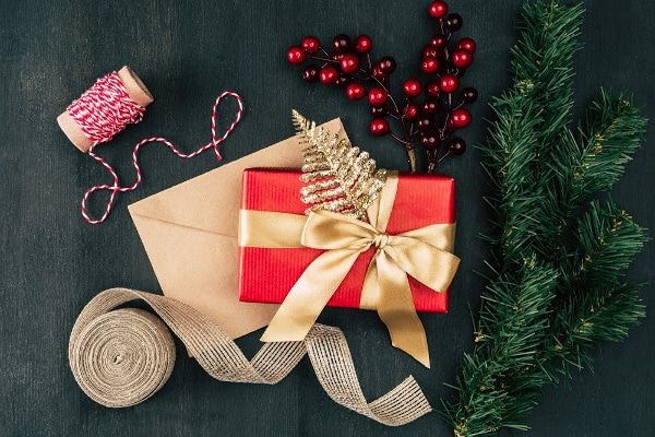 a red present with a gold bow on top of a brown envelope with ribbon, thread, berries, and greenery in the background