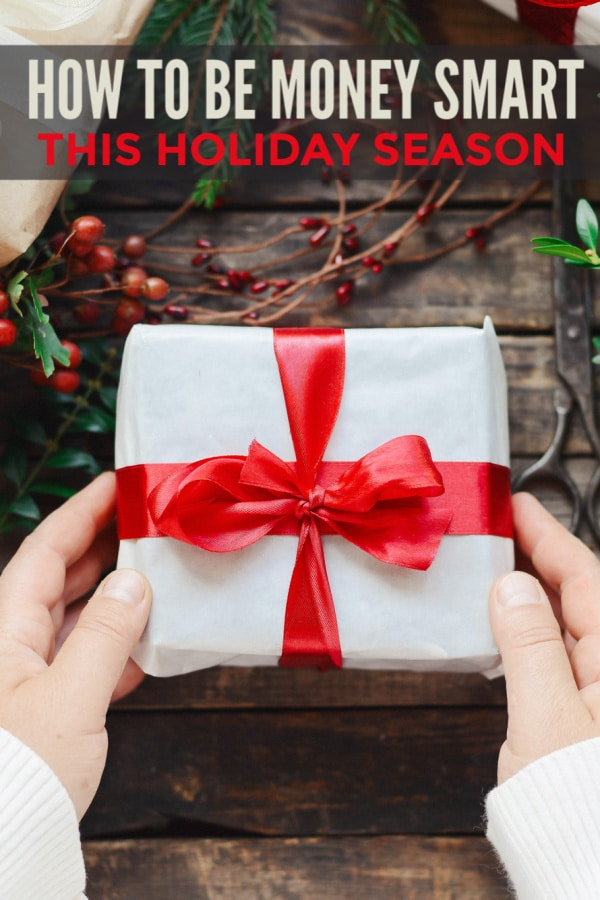 hands holding a white present wrapped with a red ribbon on a table with berries on the table with title text reading How To Be Money Smart This Holiday Season