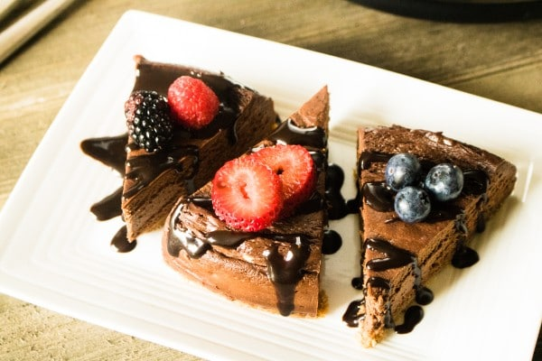 chocolate cheesecake slices topped with berries and chocolate sauce on a white plate